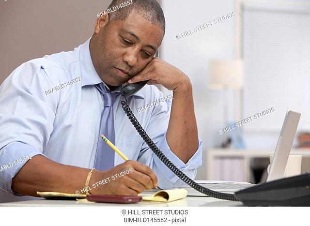 Black businessman talking on telephone and writing on notepad