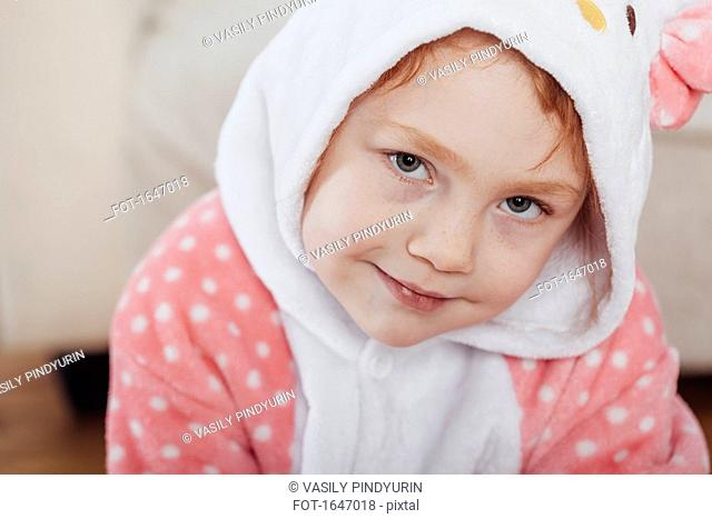 Close-up portrait of smiling girl wearing hooded shirt at home