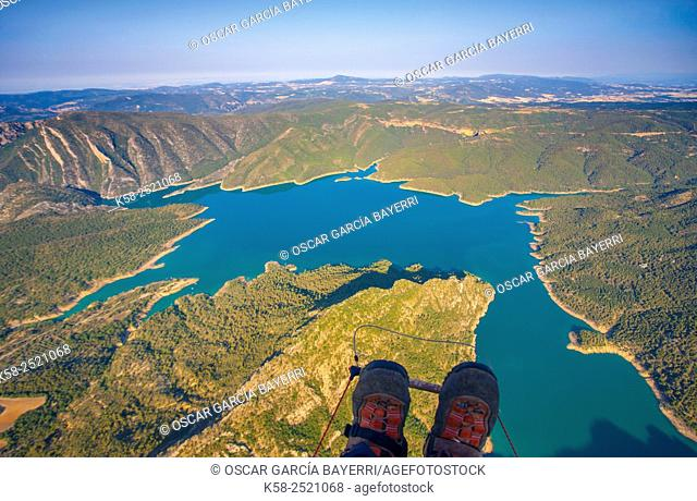 Aerial view of a paraglider flying over the Canelles reservoir in the mountains of Montec with their boots in the foreground