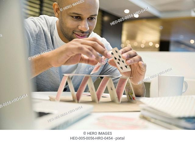 Businessman building a house of cards in office
