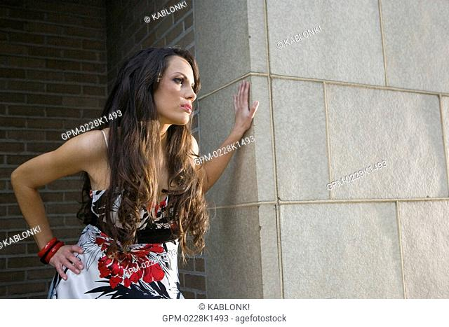 Portrait of sexy young woman in dress waiting next to building