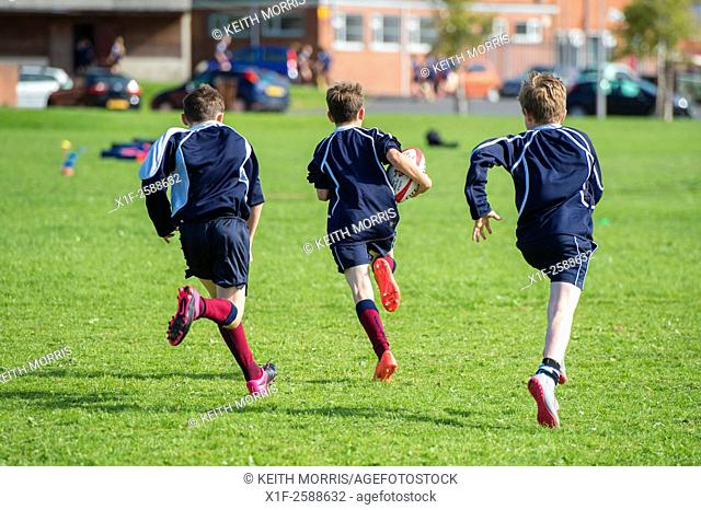 Secondary education Wales UK: physical education lesson - teenage boys playing rugby on a school games pitch field
