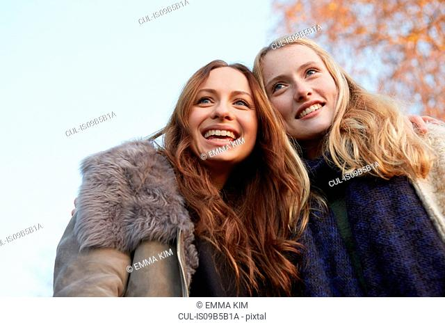 Two female friends, walking outdoors, smiling