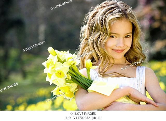A portrait of a young girl holding a bunch of daffodils, smiling