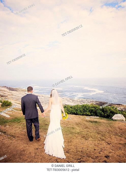 Rear view of married couple walking by sea
