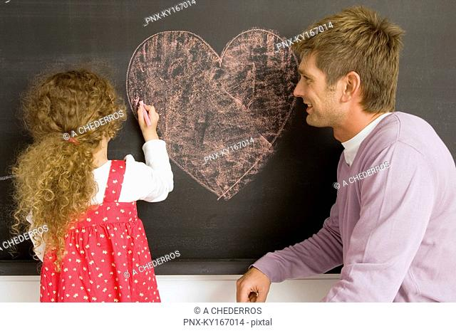 Girl drawing on a blackboard with her father watching her