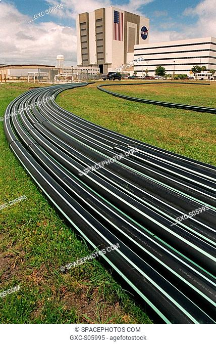 05/31/2000 --- A bundle of flexible pipes arcing toward the Vehicle Assembly Building left and Operations Support Building right presents an artistic design to...