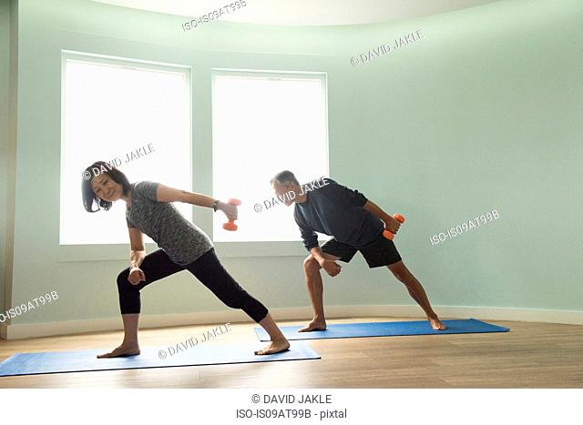 Mature couple on yoga mats exercising using dumbells
