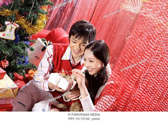 Young couple opening a Christmas gift box, smiling