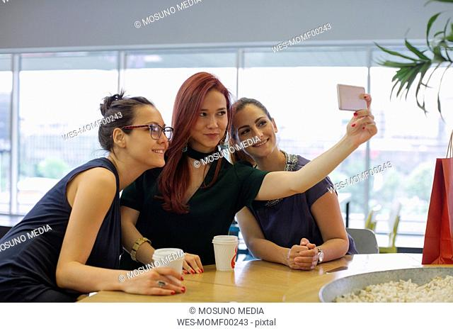 Girl friends on a shopping spree meeting in a coffee shop, taking selfies