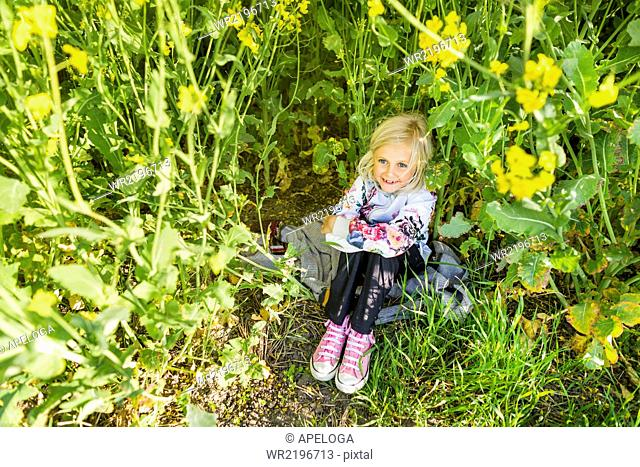High angle view of happy girl sitting amidst plants at rapeseed field