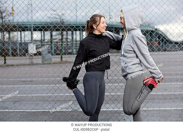 Two female runner friends stretching legs by wire fence