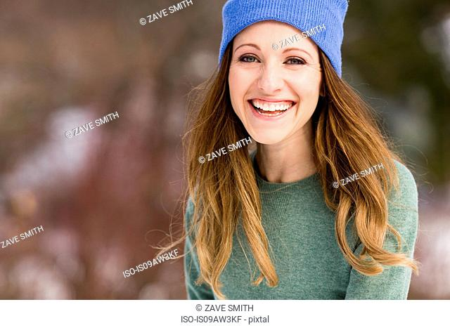 Portrait of happy young woman wearing knit hat