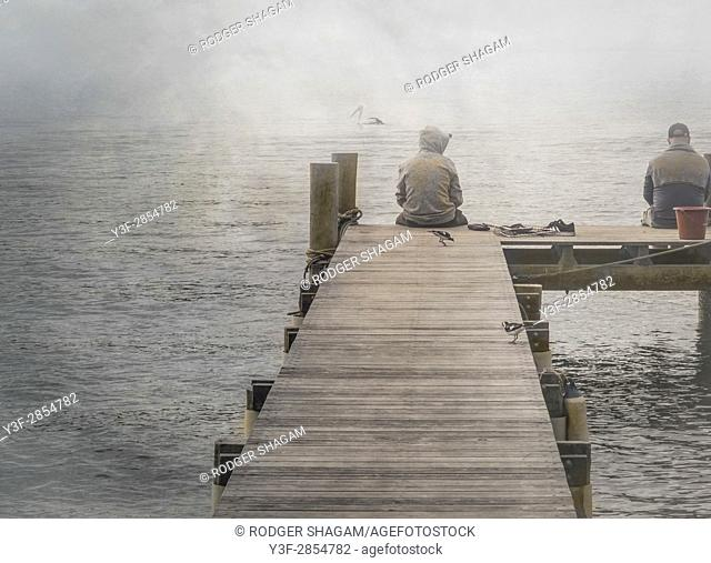 Two men sitting on a jetty in the mist. One fishing
