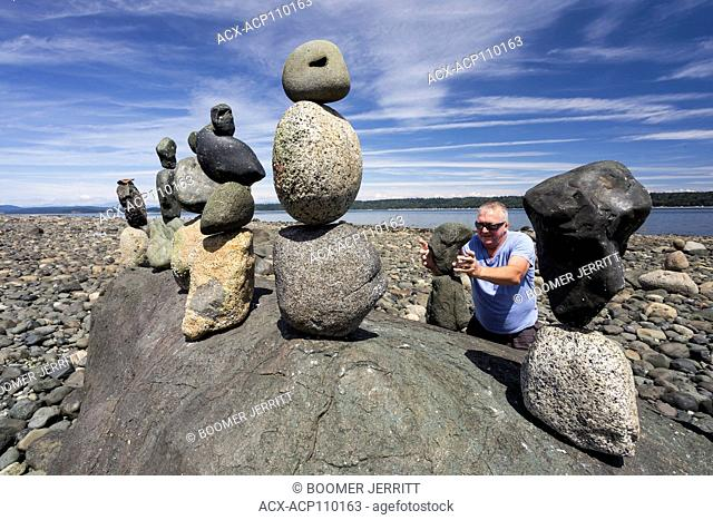 A practitioner of the art of rock balancing has a field day at low tide along the shores of Discovery Passage, Campbell River, Vancouver Island