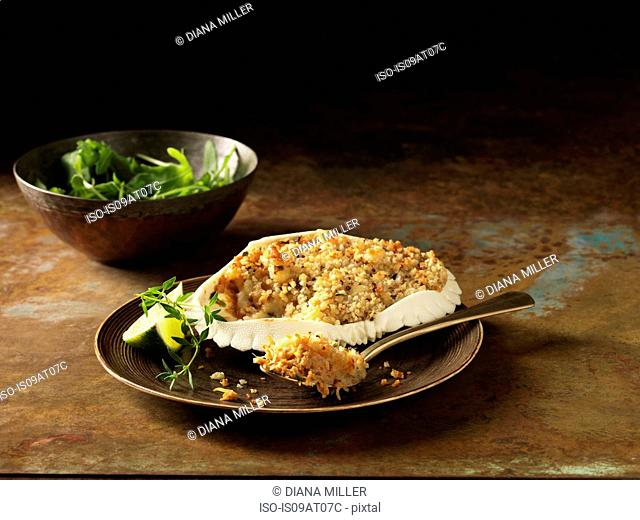 Still life of Orkney crab gratin in crab shell with bowl of mixed salad and lime