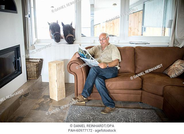 Walter Kau, head of business of Skandwood-Horsehouse GmbH, sits in his living room and behind him a horse sticks his head through the window
