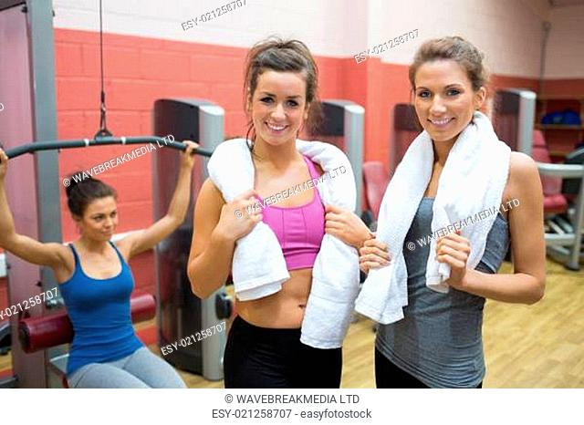 Two women with towels with woman using weight machine in gym
