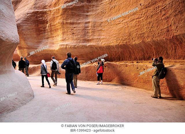 Tourists in the Siq, the one kilometer long canyon that leads to the Nabataean city Petra, Unesco World Heritage Site, near Wadi Musa, Jordan, Middle East