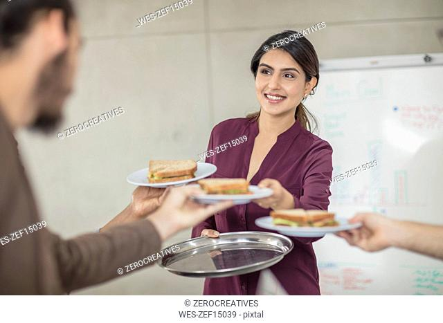Woman serving sandwiches for colleagues in office