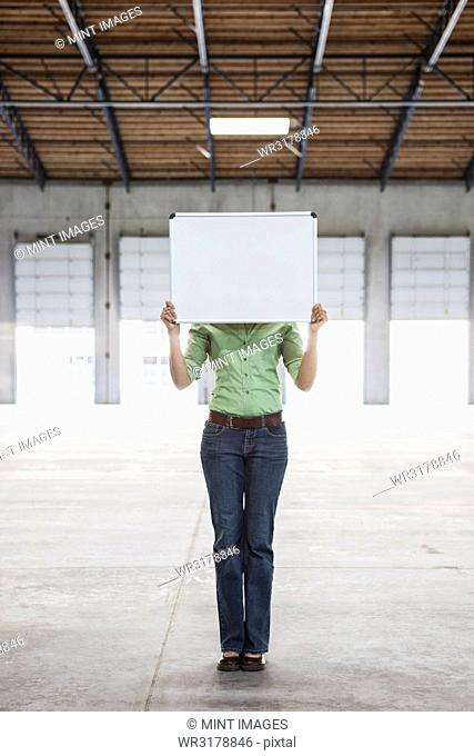 Woman holding up a blank slate in an empty warehouse space