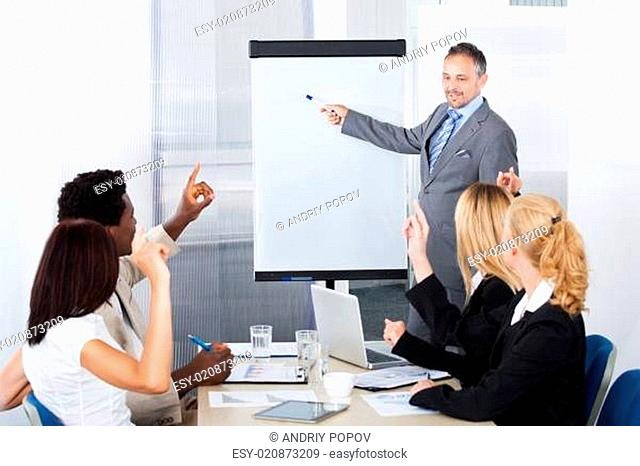 Businesspeople Looking At Man Explaining