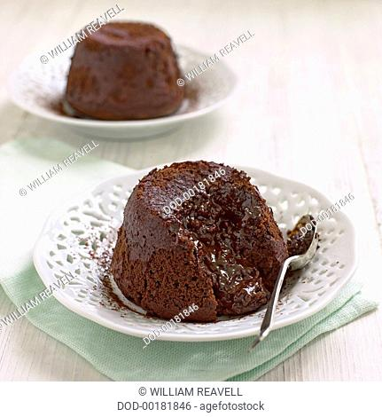 Chocolate fondant served on white dishes with spoon, close-up