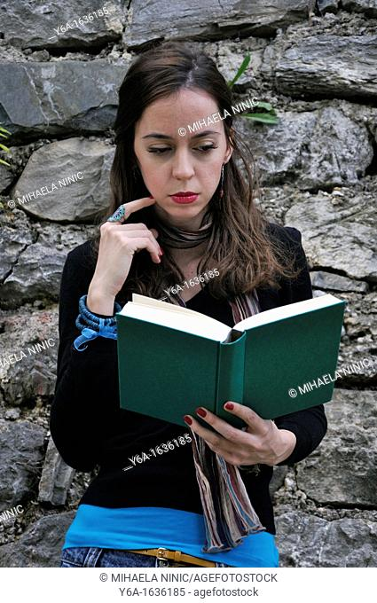 Young woman standing outdoors reading book