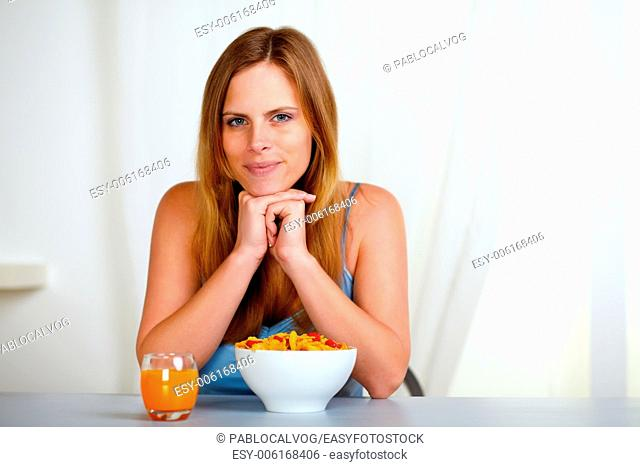 Portrait of a relaxed pretty young woman at breakfast at home indoor