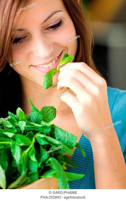 Woman smelling mint leaves Mentha sp.
