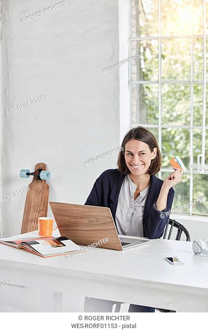 Smiling businesswoman using laptop on desk holding card