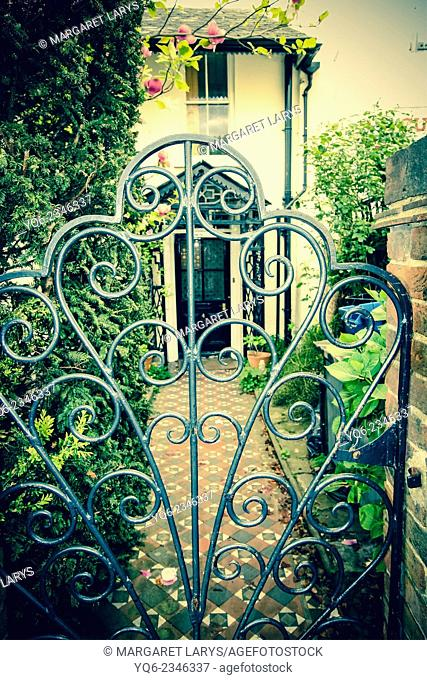 A beautiful cast iron garden gate with the old house in the background, England, United Kingdom