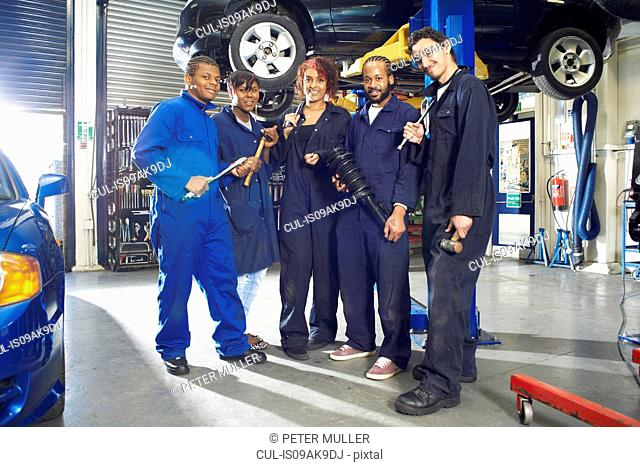 Portrait of five college students beneath car in garage workshop