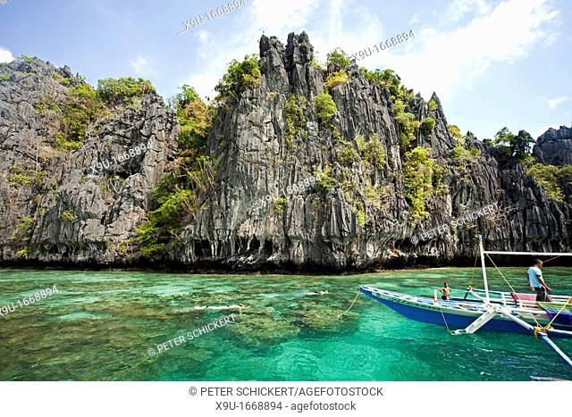 typical outrigger boat and tourists snorkelling at the small lagoon of Miniloc Island, El Nido, Palawan, Philippines, Asia