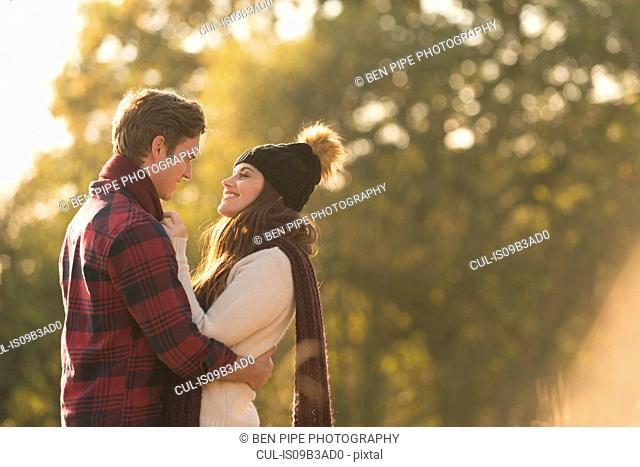 Young couple in rural setting, face to face, smiling
