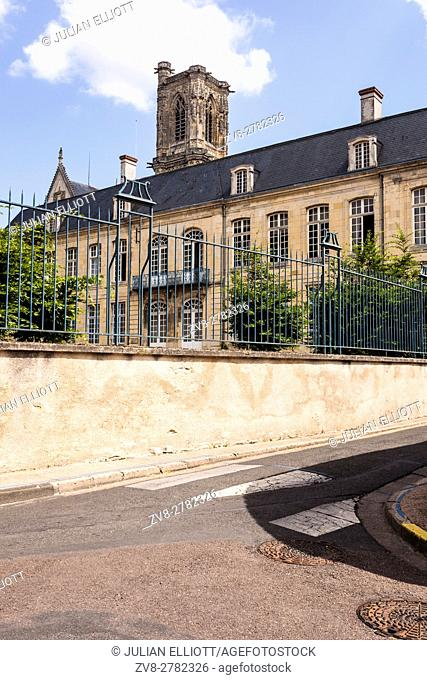 The cathedral of Saint-Cyr-et-Sainte-Julitte in Nevers, France peaking over a school building