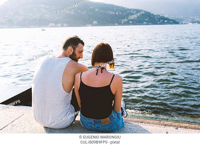 Rear view of young couple sitting on waterfront, Lake Como, Lombardy, Italy