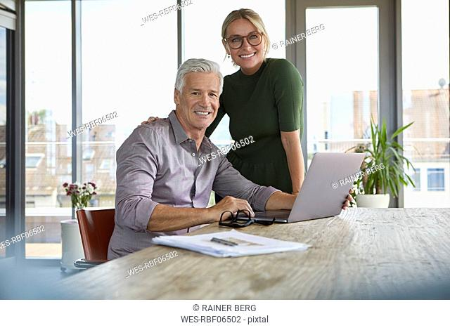 Portrait of smiling mature couple with laptop on table at home