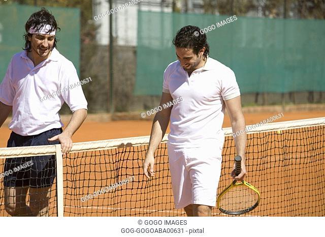 Male tennis players walking by net
