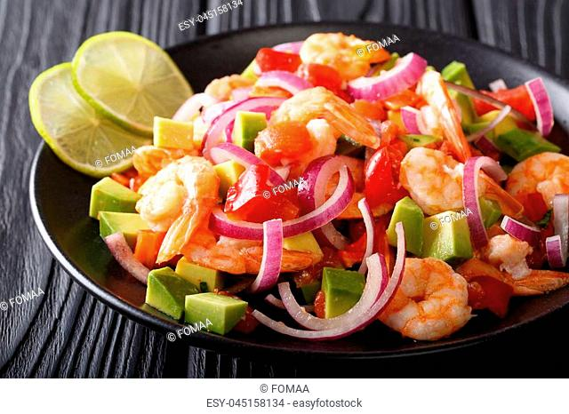 Traditional ceviche seafood with vegetables and lime close up on a plate on the table. horizontal
