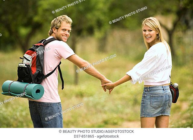 Young couple walking hand in hand in the country