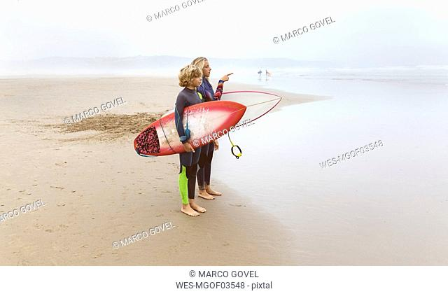 Spain, Aviles, two young surfers on the beach