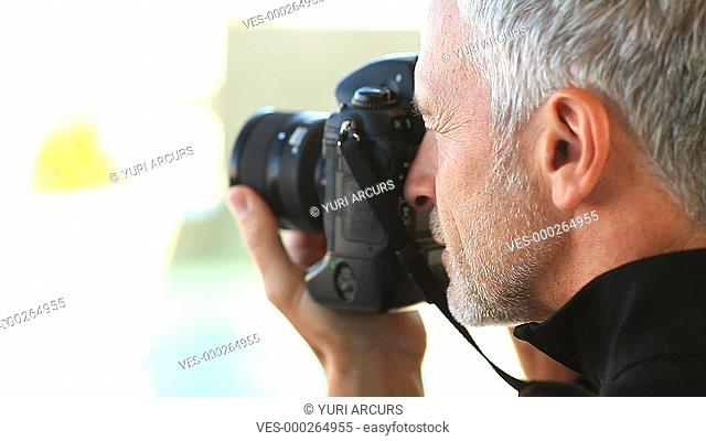 A mature male photographer taking pictures