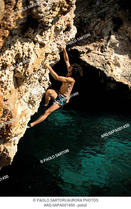 Man doing psicobloc in Mallorca, Spain. Psicobloc is a rock climbing discipline where the climber climbs without rope and other safety gear on selloffs