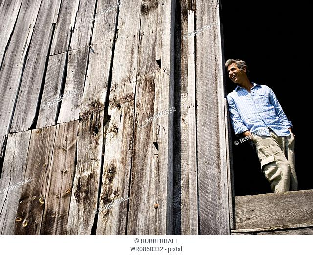 Low angle view of a man leaning against a wooden wall