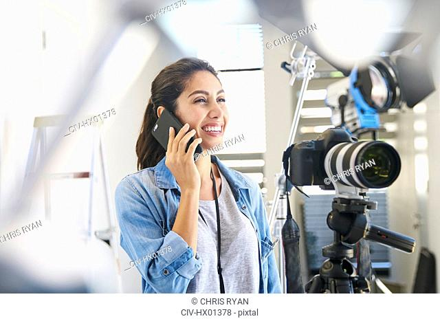 Smiling female photographer talking on cell phone behind camera in studio