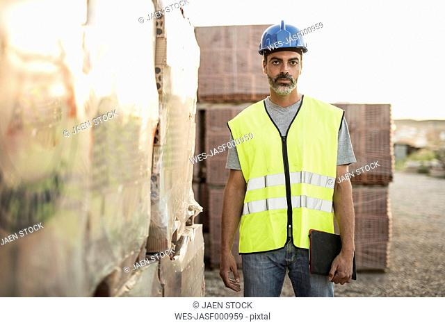 Construction worker standing in front of packaged bricks