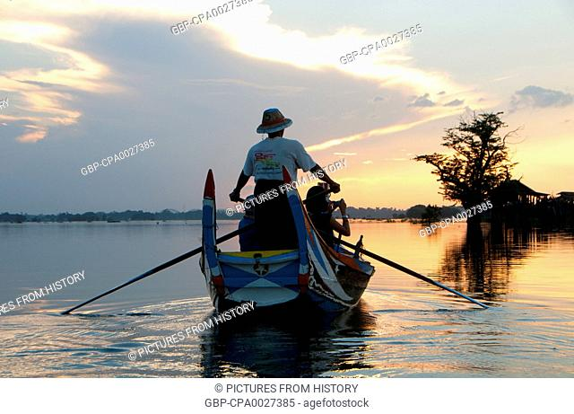 Burma / Myanmar: At sunset a boatman steers tourists close to the U Bein Bridge, the longest teakwood bridge in the world, Taungthaman Lake, near Amarapura