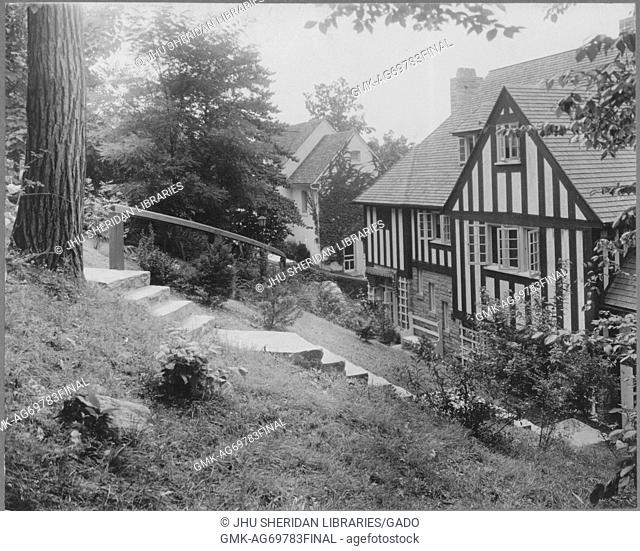 Partial view of a half-timbered and stone home with a chimney, a dormer window, standard windows, and a long set of steps with a railing leading to its entrance