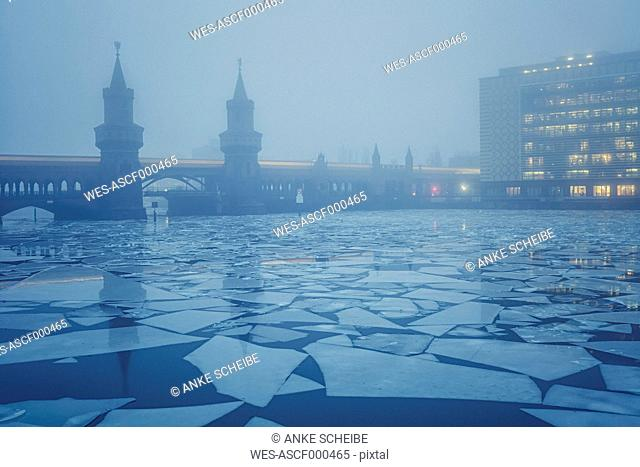 Germany, Berlin, view to Oberbaum Bridge with driving underground train at fog in winter